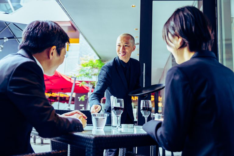 Waiter greeting his guests to the restaurant
