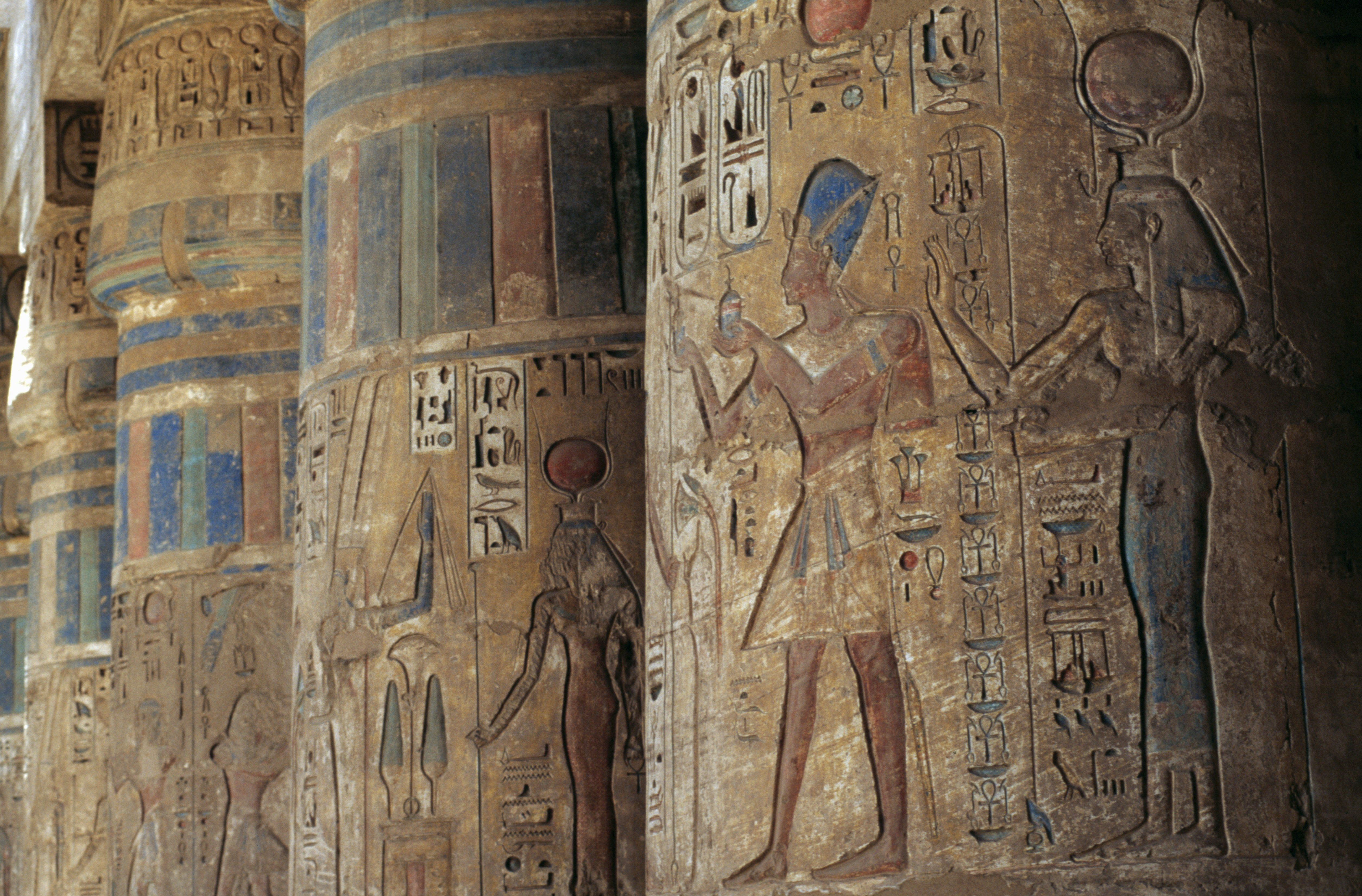 Detail of colorful images and symbols typically Egyptian in natuon carved into large stone shafts
