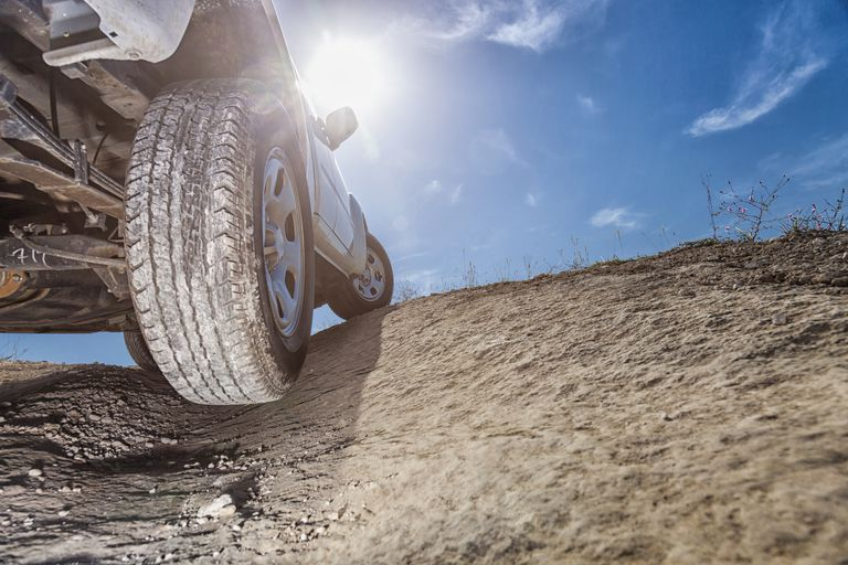 Low-angle view of the tire of a truck driving off-road
