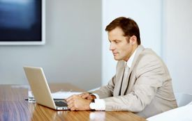 Executive working on laptop in boardroom