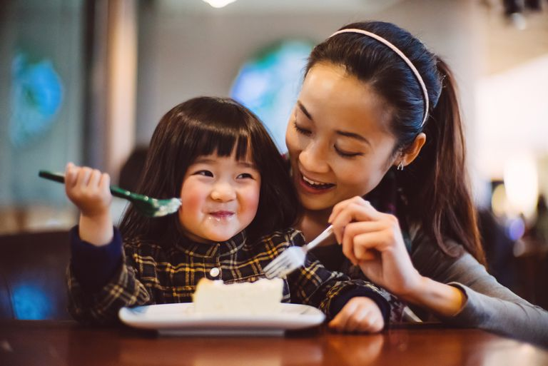 Mom & toddler girl having cake joyfully in cafe