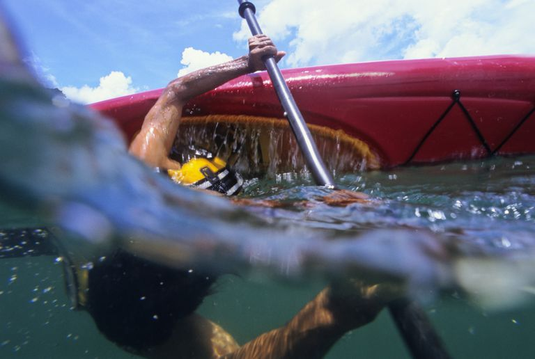 A partially-underwater view of a man rolling a kayak