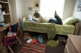 Young woman lying on bed in student dorm, writing in exercise book