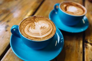 Two cups of coffee in blue cups on a wooden table close up