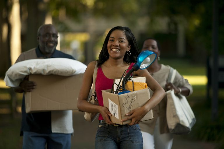 Young woman moving in to dorm, with parents behind her.