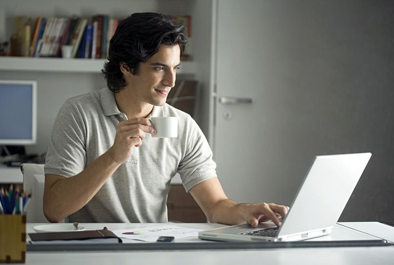 Young man sitting at desk, using laptop and drinking coffee