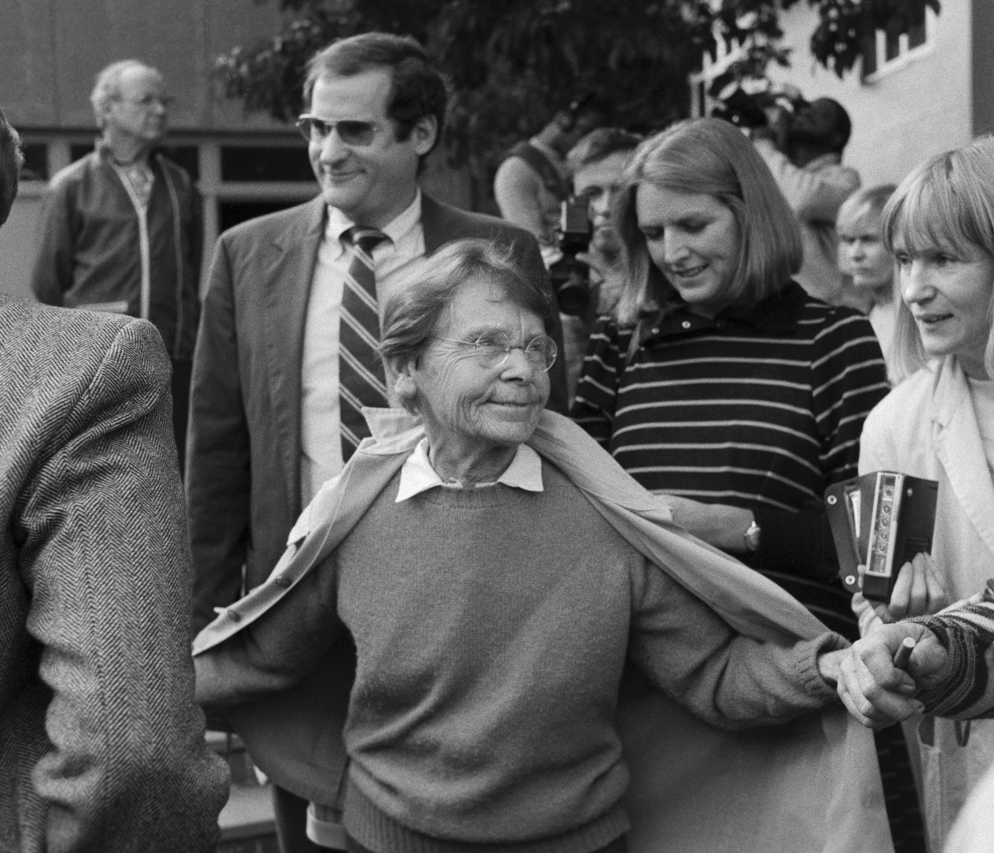 Barbara McClintock, Nobel Prize-winning geneticist, is shown surrounded by people, holding her coat open.