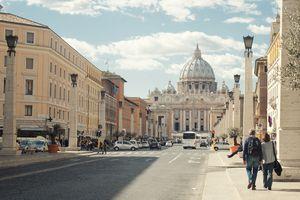 Couple walking on sidewalk in Rome.