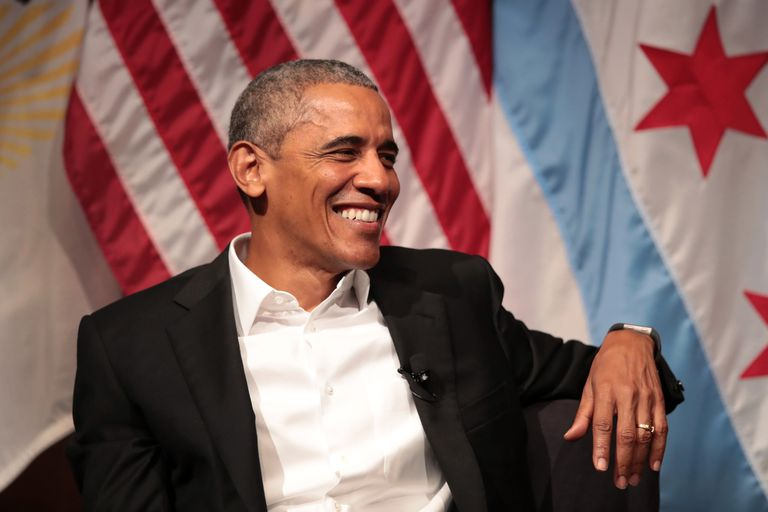 Smiling Barack Obama sits beside an American flag and speaks on civic engagement at the University of Chicago