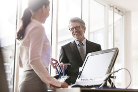 Businessman showing credentials to businesswoman at front desk