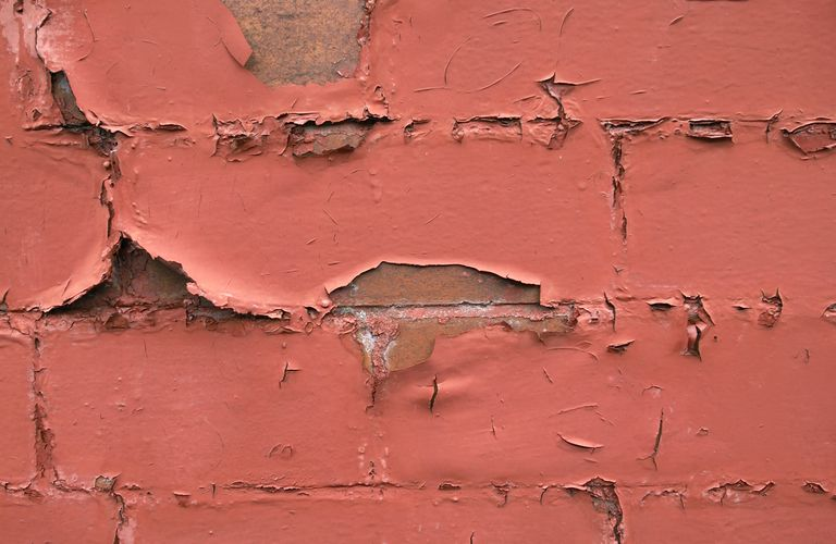 Detail of paint peeling of a brick wall
