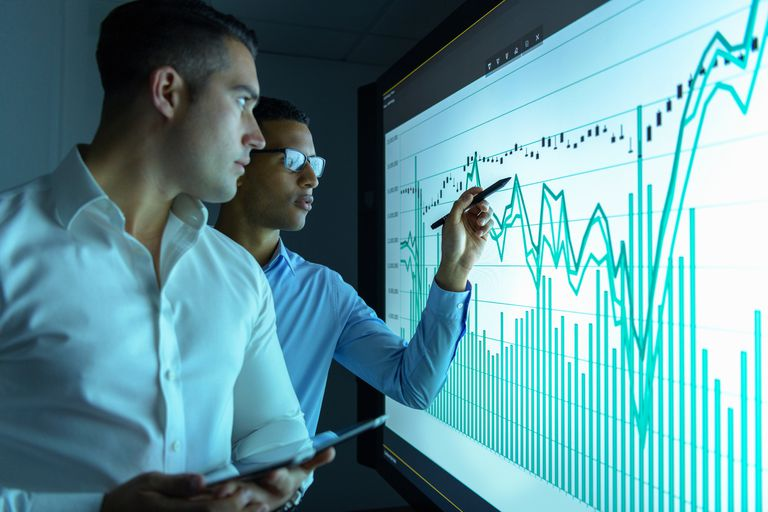 Businessmen studying graphs on an interactive screen in business meeting