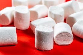 Marshmallows on a red surface.