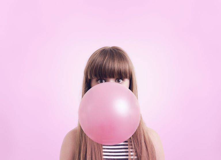 Woman blowing large bubble gum bubble before pink background