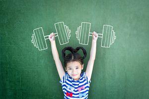 Girl lifting weights on blackboard