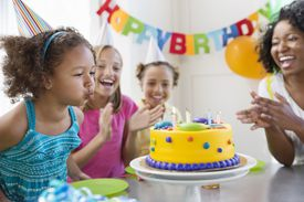 Little girl blowing out birthday candles at party with family and friends