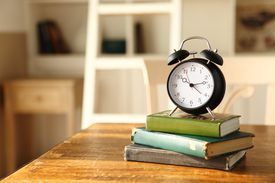 Alarm clock atop a stack of books
