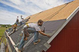 Trabajadores de la construcción trabajando en un tejado.