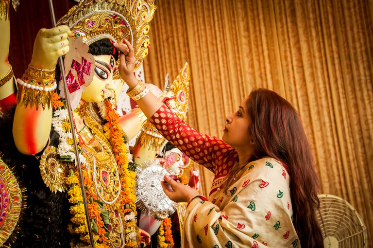 Bengali women applying vermilion to Devi Durga