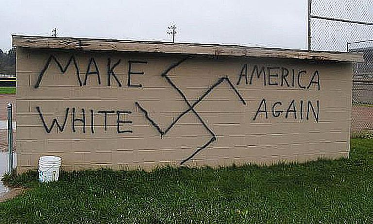 A swastika and white power message painted on a softball dugout in park in Wellsville, New York represent the surge in hate crimes that occurred after the election of Donald Trump in 2016.