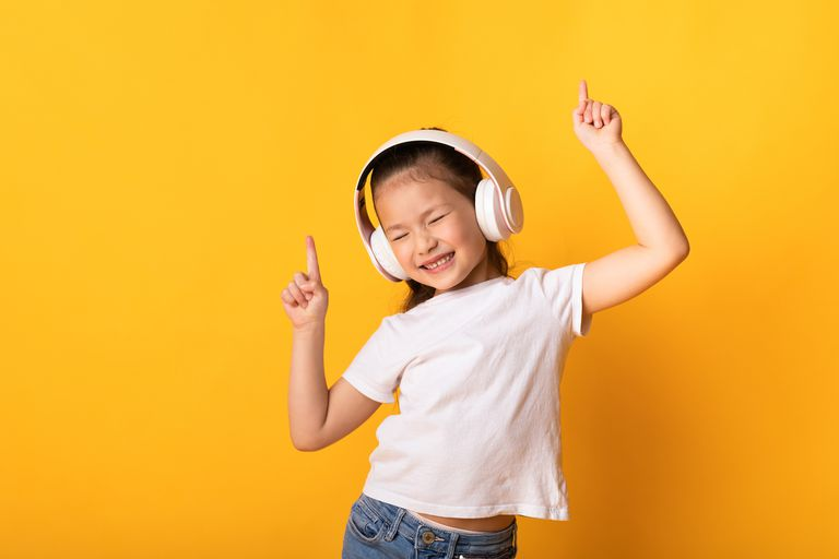 Smiling girl dancing with headphones on