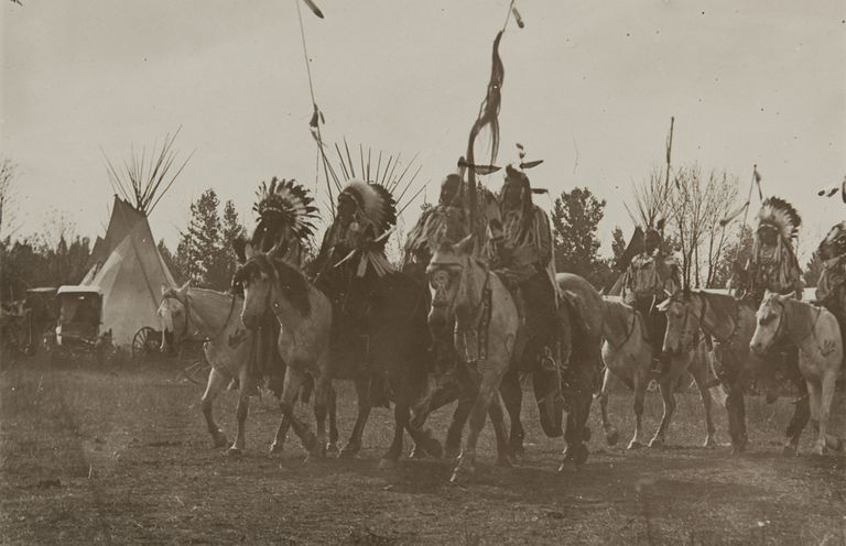 Group of Native Americans on horseback, sepia photograph.