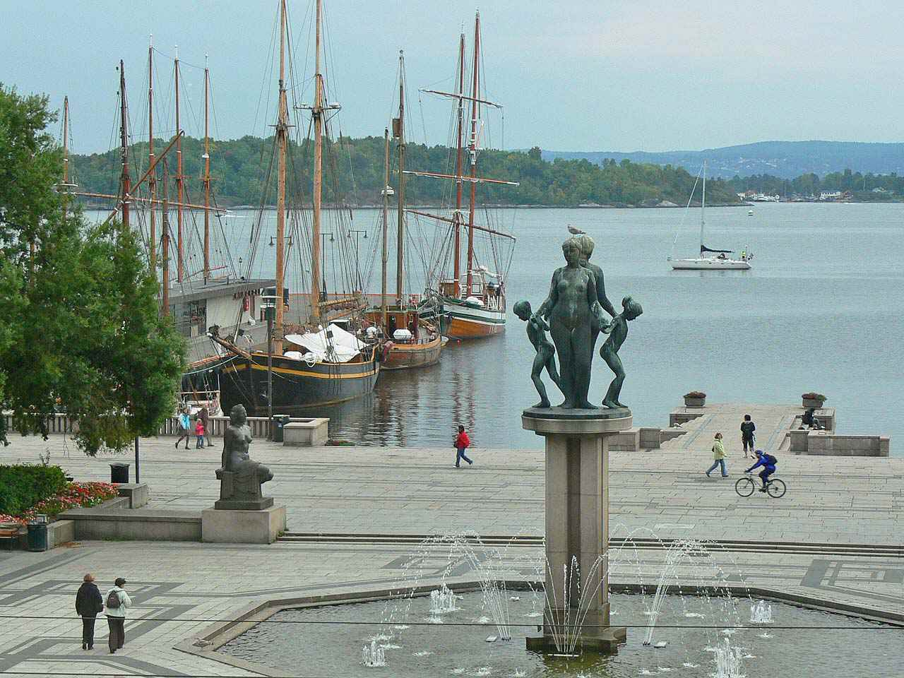 looking past a statue and fountain toward moored sailboats at a pier in water