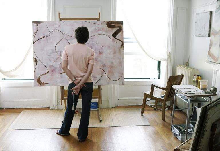 Man holding paint brush looking at painting on easel, rear view