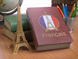 Learn and studiyng French concept. Book with French flag and Eiffel tower on the table.