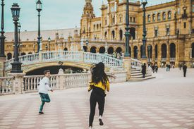 Two siblings, brother and sister, running across España square,Seville, Spain