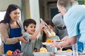 Young Hispanic family volunteering to serve food in soup kitchen