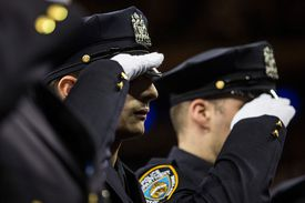 Police recruits saluting at graduation ceremony.