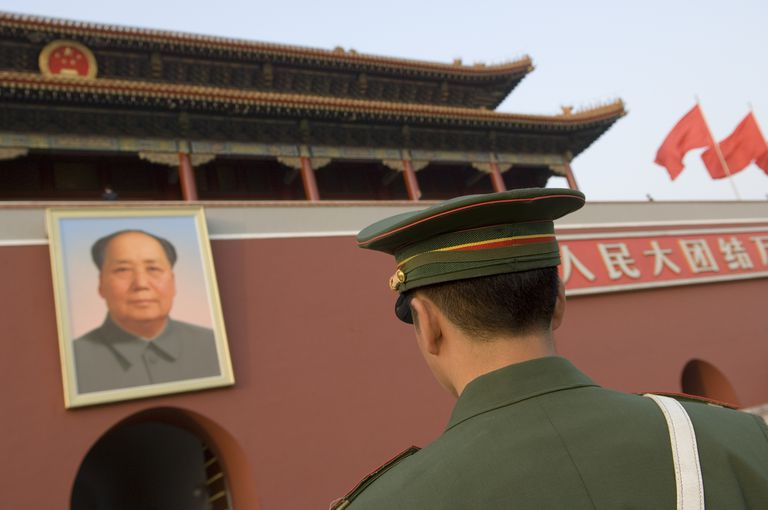 China, Beijing. Soldier standing in front of a portrait of Mao Zedong on the main entrance of the Forbidden City in Beijing