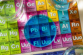 close up of set of test tubes, chemistry glassware, flask and a petri dish with blue liquid on the periodic table