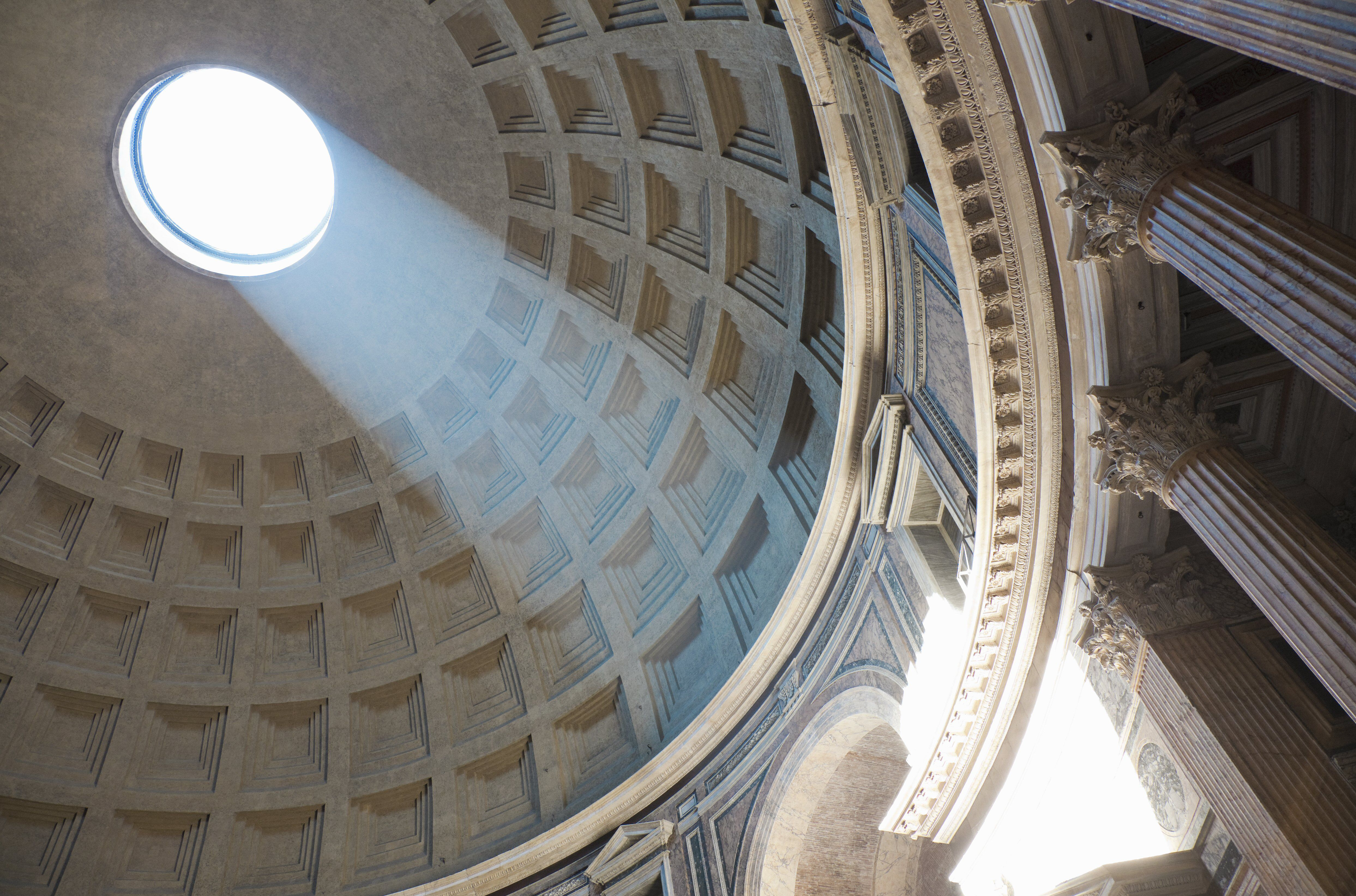 inside view of light shines through oculus, a large open hole at the top of a dome