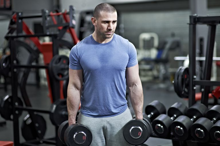 A man holding dumbbells in a gym.