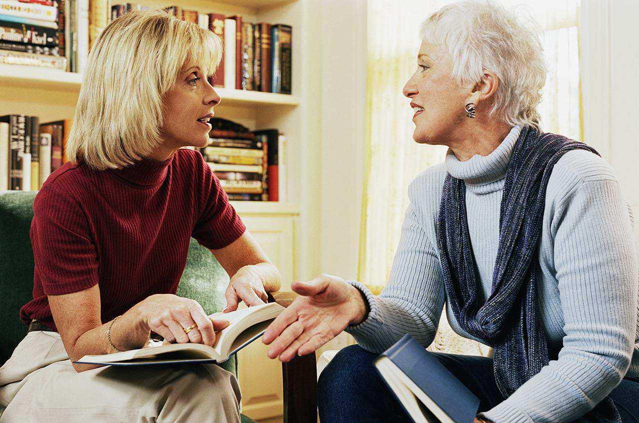 dos mujeres con libros hablando