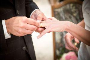 Novio colocando anillo de matrimonio en foto de esposa