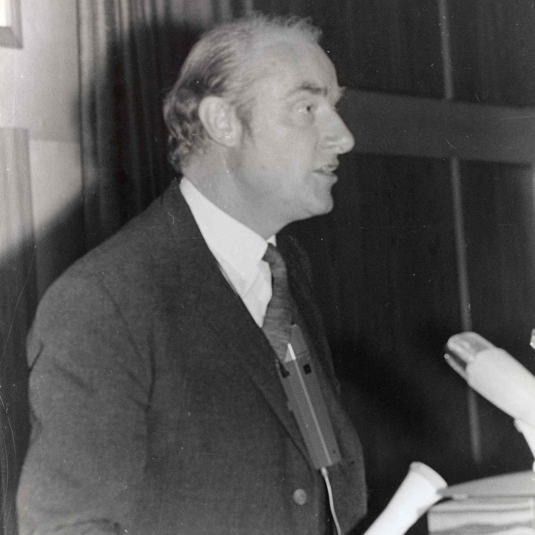 Black and white photograph of Francis Crick standing in profile.