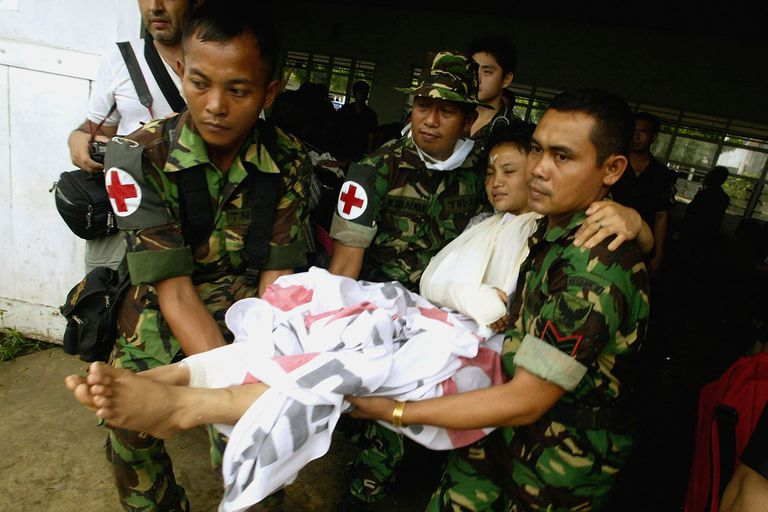 Men wearing red cross symbols carry an injured girl