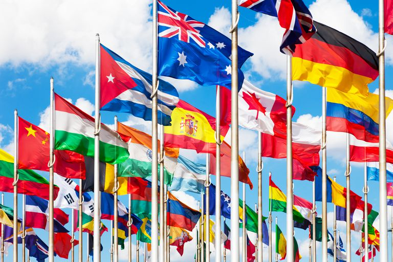 Flags of different nations flying against a blue sky