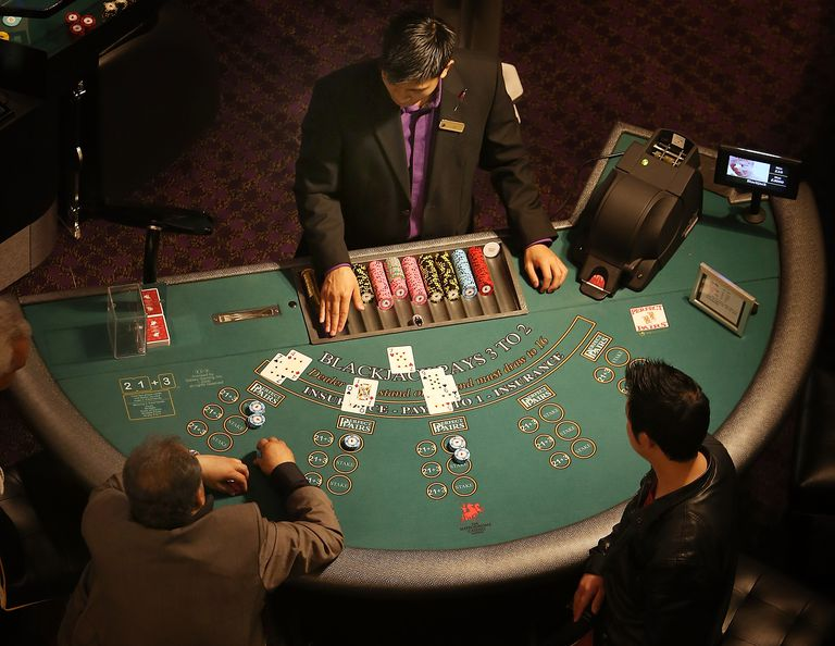 Dealer with players at a blackjack table