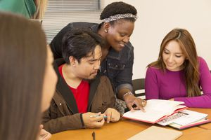Education: College students, teacher collaborate in class. Multi-ethnic, mixed age college students study together during class. The African descent instructor helps the students who have open notebooks and are sitting at the desk.