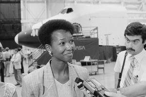 Mae Jemison speaks with reporters at a NASA facility, black and white photograph.
