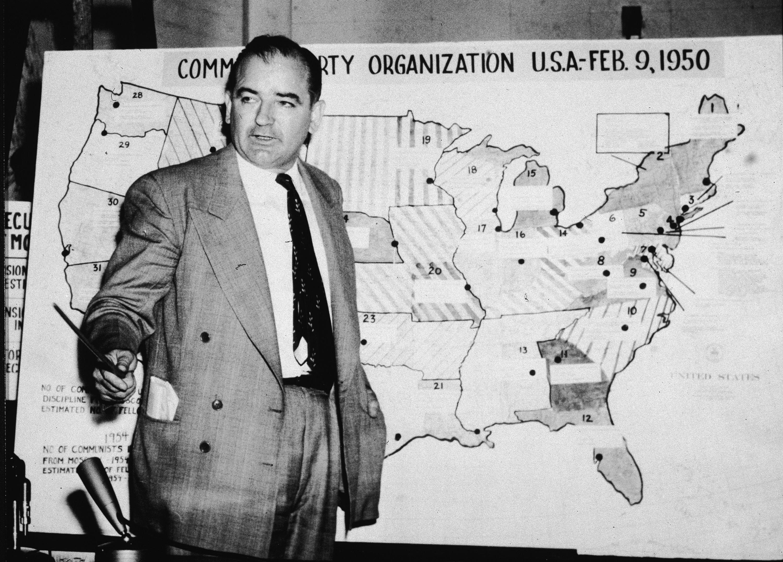 Photograph of Sen. Joseph McCarthy at a map