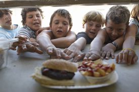 Children reaching for burger and fries