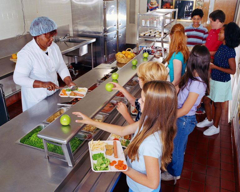 Woman serving food to schoolchildren in cafeteria.