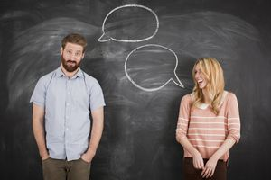 Young couple with speech bubble on blackboard, studio shot