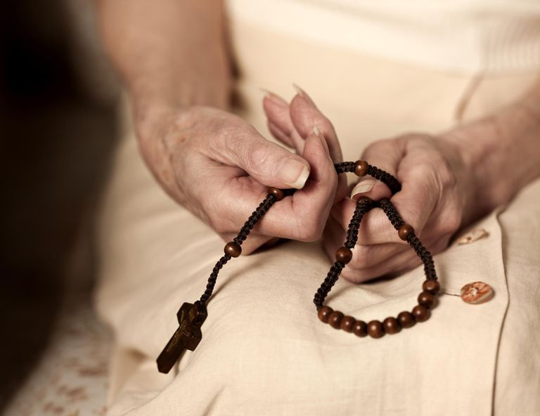 Old lady holding a rosary