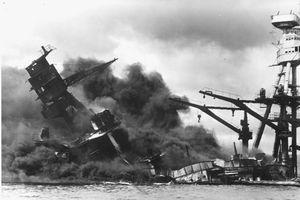 Black and white photo showing a ship damaged and left smoking during the attack on Pearl Harbor.